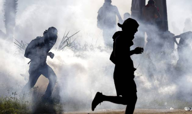 FILE - In this June 27, 2013 file photo, protesters run from tear gas dispersed by police a few miles from the soccer stadium where Spain and Italy met in a Confederations Cup soccer semifinals' match in Fortaleza, Brazil. Police are debating whether to honor a pledge to cut the use of tear gas against demonstrators, a commander said Thursday, July 18, 2013, after a small protest boiled over into rioting in one of Rio's wealthiest areas just days before a visit by Pope Francis. (AP Photo/Natacha Pisarenko, File)