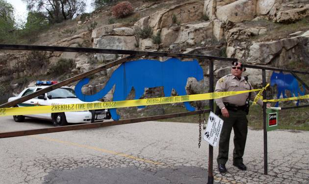 FILE - In this March 6, 2013 file photo, an officer guards the gate near at the entrance of Cat Haven, the exotic animal park in central California where a 26-year old female volunteer intern was killed by a lion, in Dunlap, Calif. Over the past few decades, as an exotic animal trade boomed and Americans bought up cute tiger and bear cubs, wild animal sanctuaries sprang up throughout the nation to take care of those wild animals once they grew to adult-size and were abandoned. Some of these sanctuaries focused on rescuing big wild cats. In turn, the growth in the trade of exotic animals and the number of sanctuaries that rescued them led to more humans handling predatory species and fueled an increase in wild cat-related incidents. (AP Photo/Gosia Wozniacka, File)
