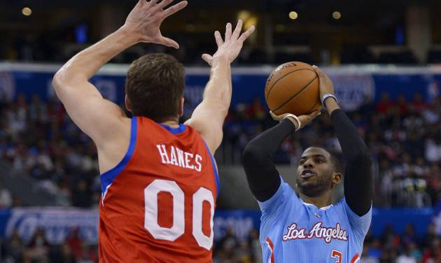 Los Angeles Clippers guard Chris Paul, right, puts up a shot as Philadelphia 76ers center Spencer Hawes defends during the first half of an NBA basketball game Sunday, Feb. 9, 2014, in Los Angeles. (AP Photo/Mark J. Terrill)