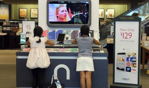 FILE - In this Friday, June 21, 2013 file photo, customers look at Nook tablets at a Barnes & Noble store in Pineville, N.C. Barnes & Noble on Wednesday, June 25, 2014 said it wants to split its retail bookstores and Nook media business into two separate public companies as it looks to boost shareholder value.  (AP Photo/Chuck Burton, File)