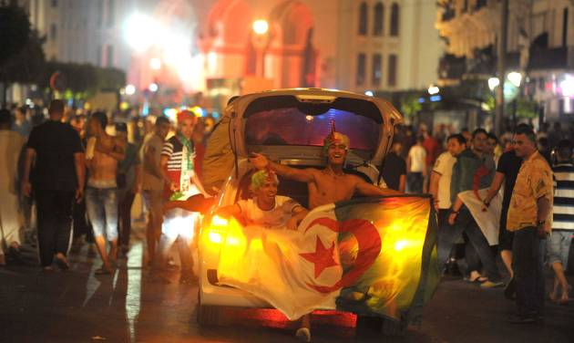 In this photo dated Thursday, June 26, 2014, Algerian soccer fans celebrate in the streets of Algiers, Algeria, after their team qualified for round of 16 following the Group H World Cup soccer match between Algeria and Russia. Algeria drew with Russia 1-1, and advanced to the round of 16 for the first time in their World Cup history. (AP Photo/Sidali Djarboub)