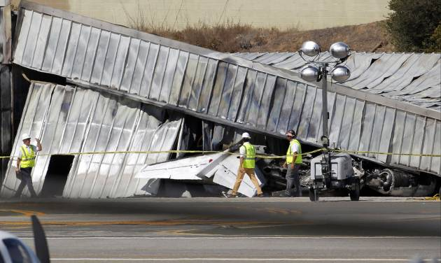 FILE - In this Sept. 30, 2013, file photo National Transportation Safety Board (NTSB) investigators walk by the tail of the private jet, which crashed into a hangar at the Santa Monica Municipal Airport in California, as they await the arrival of a crane to access the plane. As a result of the Oct. 1 federal government partial shutdown almost all of the board's 400 employees were furloughed, an NTSB spokeswoman said. Across America the government's work is piling up, and it's not just paperwork. (AP Photo/Nick Ut, File)