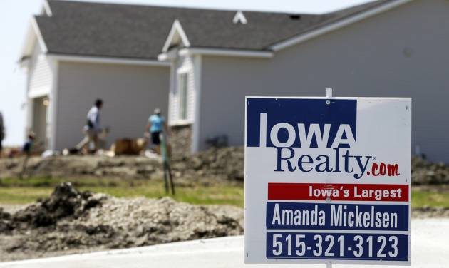 In this May 21, 2014 photo, a sign sits in front of a home for sale in West Des Moines, Iowa. The Commerce Department releases new home sales for May on Tuesday, June 24, 2014. (AP Photo/Charlie Neibergall)