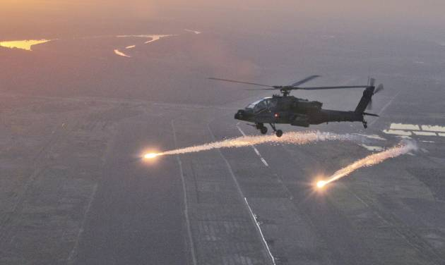 FILE - This Oct. 8, 2011, photo released by the U.S Army National Guard shows an AH-64D Apache Longbow with the South Carolina Army National Guard releasing flares during a test over Camp Tajo, Iraq. The Army has lost an initial Senate skirmish over a hotly disputed plan to take Apache attack helicopters away from National Guard units in a budget cutting move that has infuriated governors and state military leaders. (AP Photo/U.S. Army National Guard, Tracci Dorgan)