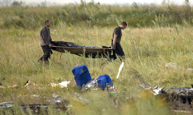 Emergency workers carry the body of a victim at the crash site of Malaysia Airlines Flight 17 near the village of Hrabove, eastern Ukraine, Saturday, July 19, 2014. World leaders demanded Friday that pro-Russia rebels who control the eastern Ukraine crash site of Malaysia Airlines Flight 17 give immediate, unfettered access to independent investigators to determine who shot down the plane. (AP Photo/Vadim Ghirda)