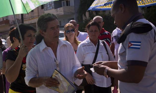 In this photo taken Jan. 13, 2014, Cuban police check identity cards of people waiting their turn to enter the U.S. Interests Section in Havana to apply for U.S. travel visas. Cubans are taking advantage of a travel reform that went into effect a year ago, when the government scrapped an exit visa requirement that for five decades had made it difficult for most islanders to go abroad. (AP Photo/Ramon Espinosa)