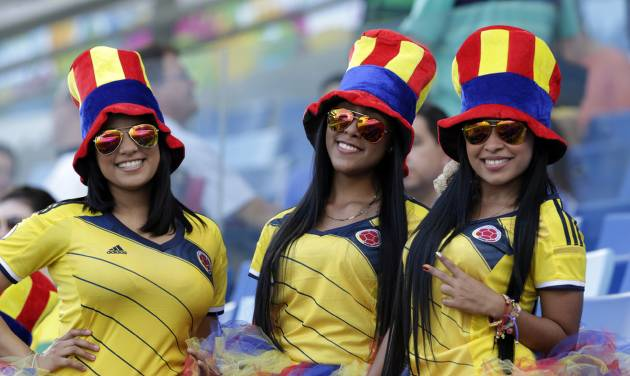 Fans of the Colombia team smile posing for the photographer before the group C World Cup soccer match between Japan and Colombia at the Arena Pantanal in Cuiaba, Brazil, Tuesday, June 24, 2014. (AP Photo/Dolores Ochoa)