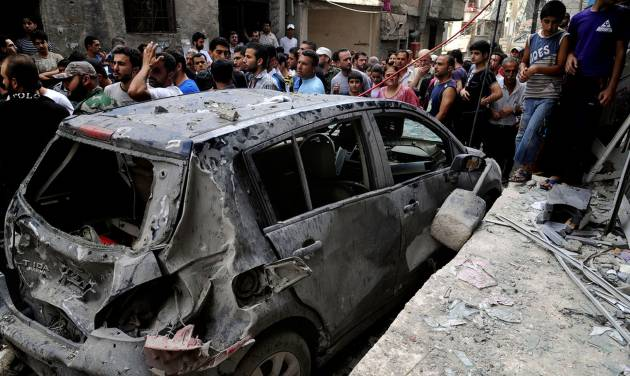 In this photo released by the Syrian official news agency SANA, Syrians investigate a damaged vehicle after two suicide bombings hit security compounds in Damascus, Syria, Wednesday, June 23, 2013. Syrian activists and state media say several have been killed in two suicide bombing attacks on security compounds in the capital, Damascus. The state-run news agency says three suicide bombers blew themselves up while trying to break into the Rukneddine police station. (AP Photo/SANA)