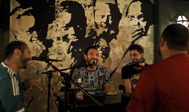 In this Monday, July 7, 2014 photo, Filipino Syrian rapper Nasser Shorbaji, 29, center, and Lebanese Marwan Alameh, 32, second right, laugh during a live broadcast of their show 'Bar Fight' at Radio Beirut, in Lebanon. The duo are among a host of Lebanese graffiti artists and rappers trying to re-engage disaffected youth in a debate about the country's latest wave of political turmoil and the woes of the greater Middle East. (AP Photo/Bilal Hussein)