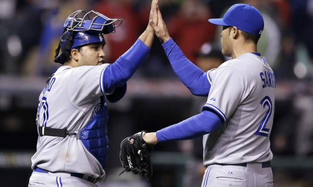 Toronto Blue Jays' Dioner Navarro, left, and Sergio Santos celebrate after the Blue Jays defeated the Cleveland Indians 3-2 in a baseball game, Friday, April 18, 2014, in Cleveland. (AP Photo/Tony Dejak)