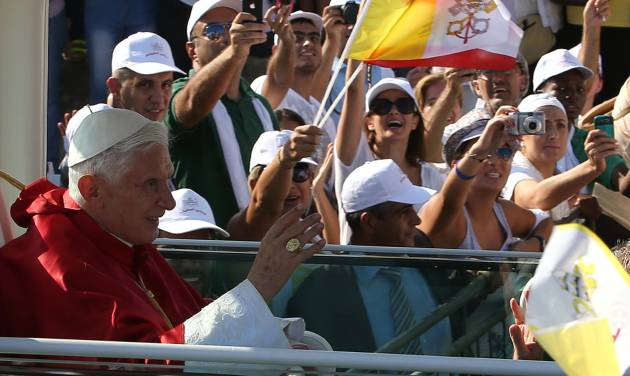 """Pope Benedict XVI, waves to Lebanese faithful from his popemobile on arrival to held mass on the waterfront in downtown Beirut, Lebanon, Sunday Sept. 16, 2012. The Pope celebrated an open-air mass for tens of thousands of pilgrims from across the Middle East, saying Christians must do their part to end the """"grim trail of death and destruction"""" in the region. (AP Photo/Hussein Malla)"""