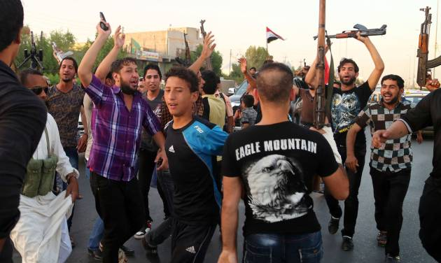 Shiite tribal fighters raise their weapons and chant slogans against the al-Qaida-inspired Islamic State of Iraq and the Levant (ISIL) in Basra, Iraq's second-largest city, 340 miles (550 kilometers) southeast of Baghdad, Iraq, Sunday, June 15, 2014. Emboldened by a call to arms by the top Shiite cleric, Iranian-backed militias have moved quickly to the center of Iraq's political landscape, spearheading what its Shiite majority sees as a fight for survival against Sunni militants who control of large swaths of territory north of Baghdad. (AP Photo/ Nabil Al-Jurani)