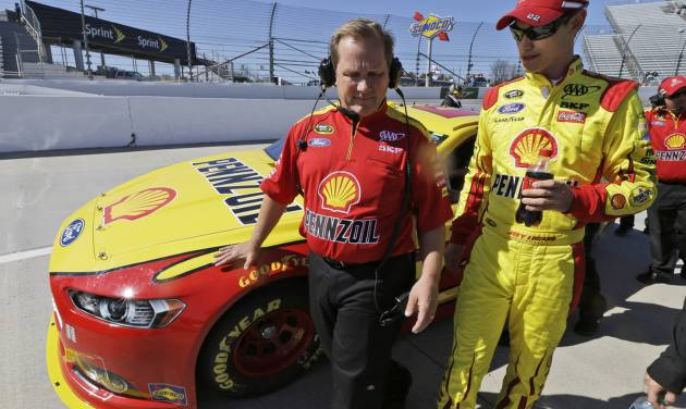 Joey Logano, right, talks with crew chief Todd Gordon during qualifying for Sunday's NASCAR Sprint Cup auto race at Martinsville Speedway in Martinsville, Va., Friday, April 5, 2013.  (AP Photo/Steve Helber)