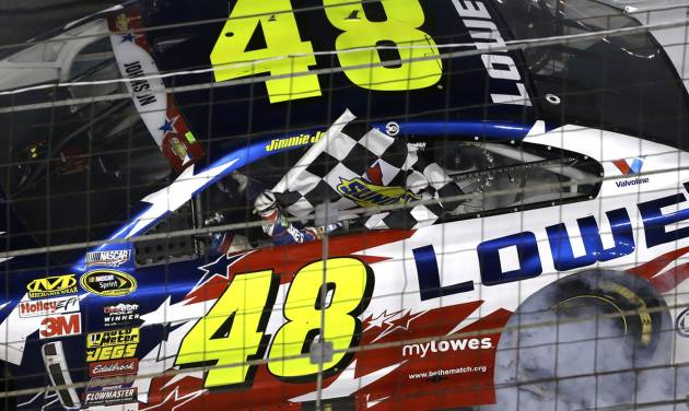 Driver Jimmie Johnson holds the checkered flag after winning the NASCAR Sprint Cup series Coca-Cola 600 auto race at the Charlotte Motor Speedway in Concord, N.C., Sunday, May 25, 2014. (AP Photo/Gerry Broome)