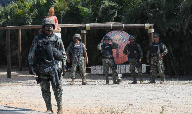 Mexican navy marines stand at a roadblock due to stepped up security after masked armed men broke into a beach home, raping six Spanish tourists who had rented the house in Acapulco, Mexico, Tuesday Feb. 5, 2013. According to the Mayor of Acapulco, five masked men burst into a house the Spaniards had rented on the outskirts of Acapulco, in a low-key area near the beach, and held a group of six Spanish men and one Mexican woman at gunpoint, while they raped the Spanish women before dawn on Monday. (AP Photo/Bernandino Hernandez)