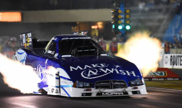 In the photo provided by the National Hod Rod Association, Tommy Johnson Jr. races to the number one qualifying position for the O'Reilly Auto Parts Route 66 NHRA Nationals drag races with a run of 3.999 seconds at 317.19 mph in Joliet, Ill. on Saturday, June 28, 2014. (AP Photo/NHRA, Teresa Long)