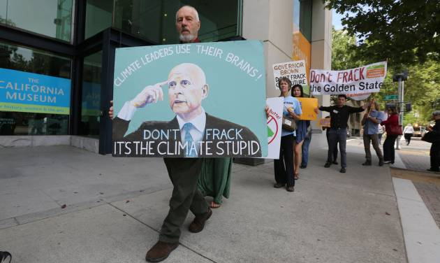 Richard Gray, left,  joins others in a demonstration calling on Gov. Jerry Brown to end hydraulic fracturing for oil and gas, outside the auditorium  where Brown spoke about climate change at the University of California  Giannini Foundation of Agricultural Economics conference in  Sacramento, Calif., Monday, May 19, 2014.(AP Photo/Rich Pedroncelli)