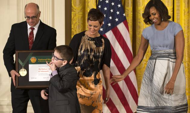 The Children's Museum of Indianapolis President and CEO Jeffrey Patchen, left, holds the museum's 2014 National Medal for Museum and Library Service as Spencer Hahn, 8, who had a stroke in-utero, whistles by his mother Erica Hahn and first lady Michelle Obama during a ceremony in the East Room of the White House, Thursday, May 8, 2014, in Washington. The National Medal is the nation's highest honor given to museums and libraries for service to the community. (AP Photo/Jacquelyn Martin)