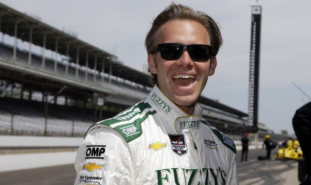 Pole-sitter Ed Carpenter laughs as he watches Dario Franchitti squeal the tires on the pace car as he pulled onto the track before the start of practice for the Indianapolis 500 IndyCar auto race at the Indianapolis Motor Speedway in Indianapolis, Monday, May 19, 2014. (AP Photo/Michael Conroy)