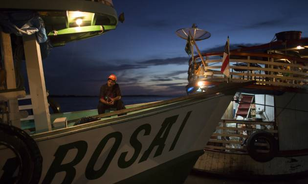 """In this May 22, 2014, photo,  a man sits on the  """"Almirante Barbosa"""" during a quick stop at the port of Manacapuru, near Manaus, Brazil. Boats like the Almirante Barbosa are the lifeline of Brazil's Amazon region, where they transport passengers and staples ranging from rice to diapers, and deliver them to remote riverside villages inaccessible any other way. (AP Photo/Felipe Dana)"""
