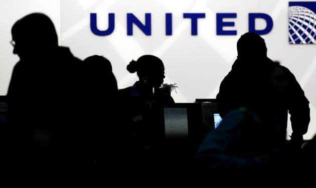 FILE - In this Saturday, Dec. 21, 2013, file photo, travelers check in at the United Airlines ticket counter at Terminal 1 in O'Hare International Airport in Chicago. Starting March 2015, elite members of United's MileagePlus will earn between 7 and 11 miles for every dollar they spend on tickets, not counting taxes. Regular members, those who fly less than 25,000 miles and spend less than $2,500 a year, will get 5 miles per dollar toward free travel. (AP Photo/Nam Y. Huh, File)
