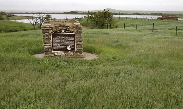 """A monument marks the Kildeer Mountain area where US soldiers clashed with Native American in 1864 Wednesday, June 11, 2014, near Killdeer, N.D. The site was surveyed by a team of archeologists when a power company wanted to run new power lines through the area. Indian tribes feared the project could disturb the remains of native people who were killed there but archeologists hired by the utility found """"nothing of consequence"""" along a 150-foot right of way. (AP Photo/Charles Rex Arbogast)"""