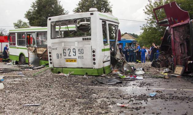 Emergency workers and investigators work at the site of the crash of a truck and a bus near Oznobishino, a settlement in the Moscow municipality, about 40 kilometers (25 miles) south of the city center, Russia, Saturday, July 13, 2013. More than a dozen people are dead after a truck carrying macadam ran into a passenger bus in an outlying area of Moscow. (AP Photo/Igor Ivashin)