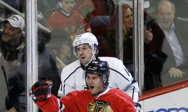 Chicago Blackhawks left wing Brandon Saad (20) celebrates his goal as Los Angeles Kings center Mike Richards skates behind during the first period of an NHL hockey game Monday, Dec. 30, 2013, in Chicago. (AP Photo/Charles Rex Arbogast)