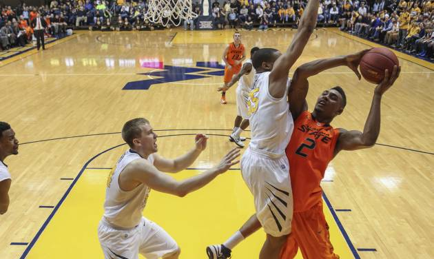 Oklahoma State's Le'Bryan Nash (2) is fouled by West Virginia's Gary Browne (14) during the first half of an NCAA college basketball game in Morgantown, W.Va., on Saturday, Feb. 23, 2013. (AP Photo/David Smith)
