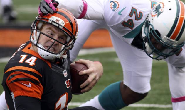 Cincinnati Bengals quarterback Andy Dalton (14) is tackled by Miami Dolphins cornerback Sean Smith (24) after a short gain in the second half of an NFL football game on Sunday, Oct. 7, 2012, in Cincinnati. Miami won 17-13. (AP Photo/Tom Uhlman)