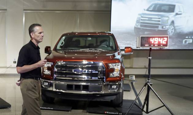 Ford Truck Group Marketing Manager Doug Scott stands next to the automaker's new aluminum-sided 2015 F-150 truck at the company's Development Center in Dearborn, Mich., Tuesday, July 22, 2014. The truck, which goes on sale this fall, is 732 pounds lighter than the outgoing model. Ford's base truck with a 3.5-liter V6 engine, will get 283 horsepower, similar to a Chevrolet Silverado but lower than a Ram. But Ford says it will have more towing capacity than both rivals, at 7,600 pounds. (AP Photo)