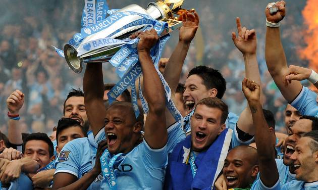 Manchester City's players captain Vincent Kompany, center, holds the Cup and celebrates with teammates after being crowned Premier League Champions, after the English Premier League soccer match between Manchester City and West Ham United at the Etihad Stadium,  Manchester, England, Sunday, May 11, 2014. (AP Photo/Rui Vieira)