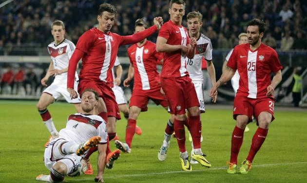 Germany's Benedikt Hoewedes, bottom, and Poland's Lukasz Szukala challenge for the ball during a friendly soccer match between Germany and Poland in Hamburg, Germany, Tuesday, May 13, 2014.  (AP Photo/Matthias Schrader)