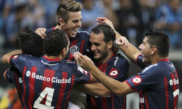 Julio Buffarini, top, of Argentina's San Lorenzo celebrates with teammates after their team defeated Brazil's Gremio during a Copa Libertadores soccer match in Porto Alegre, Brazil, Wednesday, April 30, 2014. San Lorenzo defeated Gremio in a penalty shootout. (AP Photo/Nabor Goulart)