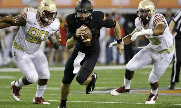 Oklahoma State quarterback J.W. Walsh (4) scrambles out of the pocket as Florida State's Eddie Goldman (90) and Arthur Williams, right, give chase in the second half of an NCAA college football game, Saturday, Aug. 30, 2014, in Arlington, Texas. FSU won 37-31. (AP Photo/Tony Gutierrez)