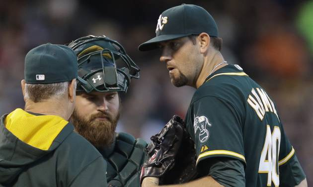 Oakland Athletics' Jason Hammel, right, speaks with pitching coach Curt Young and catcher Derek Norris in the third inning of a baseball game against the San Francisco Giants Wednesday, July 9, 2014, in San Francisco. (AP Photo/Ben Margot)