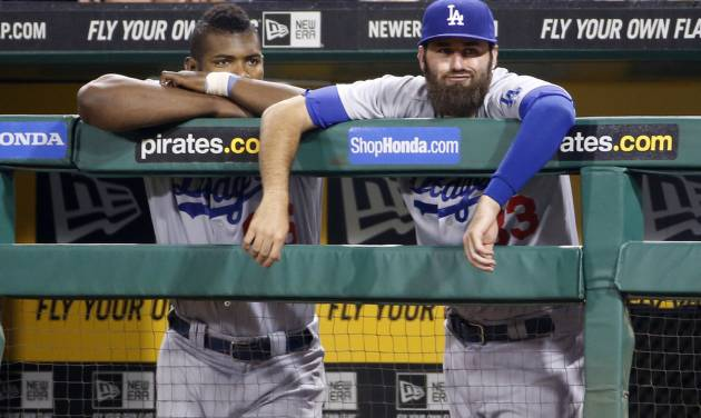 Los Angeles Dodgers' Yasiel Puig, left, and Scott Van Slyke stand in the dugout during the ninth inning of a baseball game against the Pittsburgh Pirates in Pittsburgh Tuesday, July 22, 2014. The Pirates won 12-7. (AP Photo)