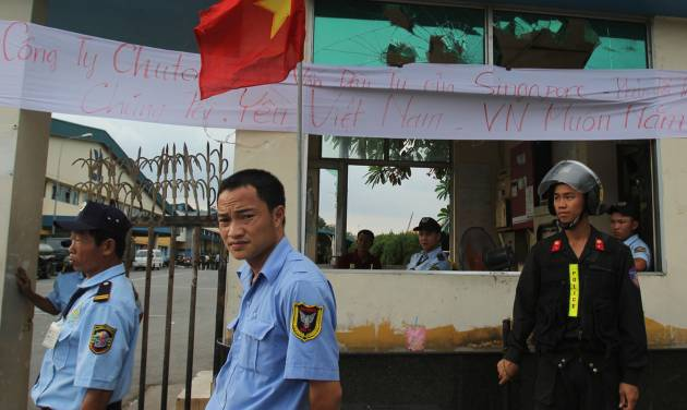 "Security staff guard the entrance to a Singaporean factory in an industrial park in Binh Duong province, Vietnam Saturday, May 17, 2014, after mobs attacked foreign owned factories following anti-China protests. Vietnam's prime minister ordered an end Saturday to all ""illegal protests"" in the country after a week of violent demonstrations against China's deployment of an oil rig in a disputed section of the South China Sea. Banner reads: ""This is a Singaporean owned company. We love Vietnam"". (AP Photo/Hau Dinh)"