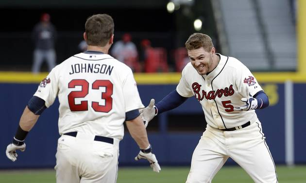 Atlanta Braves' Freddie Freeman, right, celebrates with teammate Chris Johnson after Freeman hit a single to score the game-winning run in the 10th inning of a baseball game against the Cincinnati Reds, Sunday, April 27, 2014, in Atlanta. The Braves won 1-0 in 10 innings. (AP Photo/David Goldman)