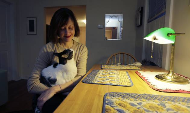 Valerie Spain poses with her pet cat at the kitchen table of her Cambridge, Mass., home, Thursday, Jan. 17, 2013.  The 57-year-old former operations manager was able to find insurance through the subsidized Commonwealth Care program created under the a Massachusetts healthcare law. She pays no premiums, but is charged a $20 co-pay for visits to her doctor's office. (AP Photo/Charles Krupa)
