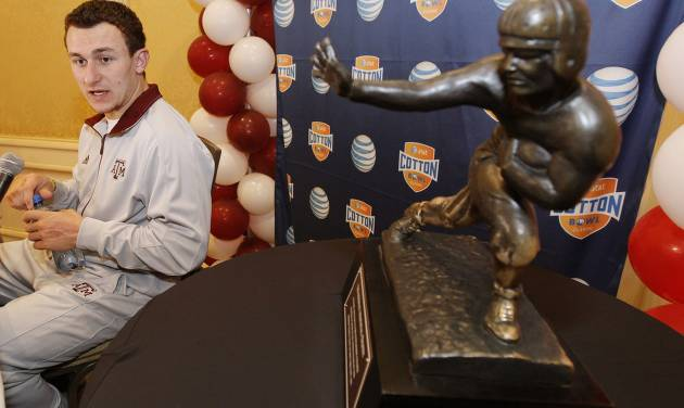 CORRECTS YEAR - Texas A&M freshman quarterback Johnny Manziel answer questions during a Cotton Bowl press conference, with a Heisman Trophy at side, at the Omni Mandalay hotel, Tuesday, Jan. 1, 2013, in Irving, Texas. Texas A&M plays Oklahoma on Jan. 4 in the Cotton Bowl in Arlington, Texas. (AP Photo/Brandon Wade)