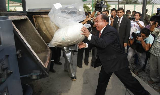 FILE - In this April 26, 2012 file photo, Interior Minister Daniel Lozada throws a bag of seized cocaine into an incinerator at a police base in Lima, Peru. Peru's defense and interior ministers have quit amid complaints from lawmakers about incompetence in the fight against Shining Path rebels. (AP Photo/Karel Navarro, File)