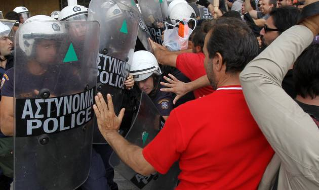 Riot police clash with protesters inside Greece's Defense Ministry in Athens, Thursday, Oct. 4, 2012. Police clashed with scores of protesting shipyard workers after they forced their way into the grounds of Greece's Defense Ministry. The workers say they have not been paid in months. (AP Photo/Thanassis Stavrakis)