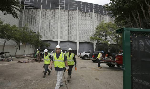 Construction workers walk out a gate outside an Astrodome loading area Tuesday, Nov. 5, 2013, in Houston. Voters are deciding whether to approve a referendum authorizing up to $217 million in bonds to turn the stadium that once hosted both baseball and football games into a giant convention center and exhibition space. (AP Photo/Pat Sullivan)