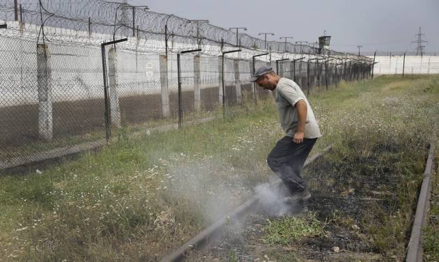 A prisoner tramples smoldering grass in a high-security facility after shelling in Donetsk, eastern Ukraine, Monday, Aug. 11, 2014. Local authorities say more than 100 prisoners have fled from a high-security facility after it was hit by shelling in the rebel stronghold of Donetsk. City council spokesman Maxim Rovensky said Monday a jail riot was precipitated by a direct rocket hit that claimed the life of at least one inmate. The fugitives include people jailed for murder, robbery and rape. (AP Photo/Sergei Grits)