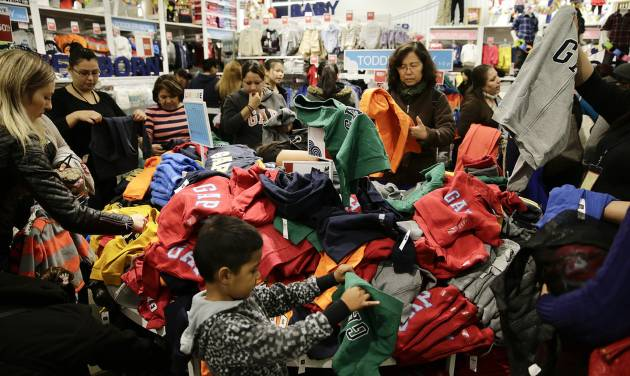 People shop at a Gap factory store at the Citadel Outlets on Thursday, Nov. 28, 2013, in Los Angeles . Instead of waiting for Black Friday, which is typically the year's biggest shopping day, more than a dozen major retailers are opening on Thanksgiving day this year. (AP Photo/Jae C. Hong)
