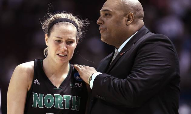 North Dakota coach Travis Brewster, right, comforts Madi Buck after losing 70-55 to Texas A&M in a first-round NCAA women's basketball game Sunday, March 23, 2014, in College Station, Texas. A&M will face James Madison in the second round Tuesday night. (AP Photo/Pat Sullivan)