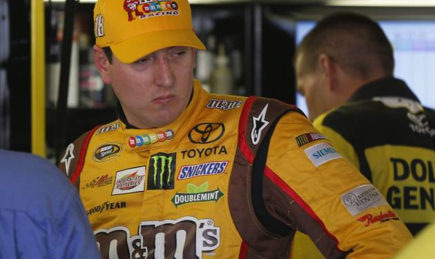 Driver Kyle Busch talks with crew members during practice for Sunday's NASCAR Sprint Cup series auto race at Kansas Speedway in Kansas City, Kan., Friday, Oct. 4, 2013. (AP Photo/Orlin Wagner)