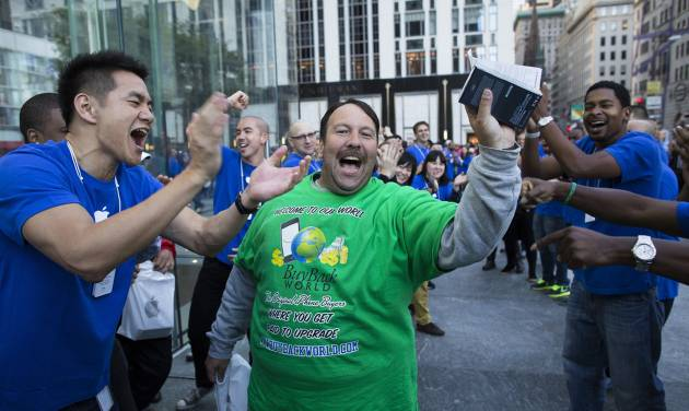 Greg Packer, 49, is cheered on as he celebrates with his newly purchased iPhone 5 in hand outside the Fifth Avenue Apple store, Friday, Sept. 21, 2012, in New York. Hundreds of people waited in line through the early morning to be among the first to get their hands on the highly anticipated phone. (AP Photo/John Minchillo)
