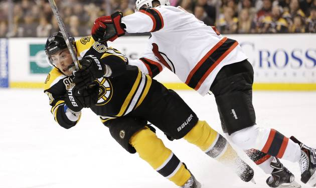 Boston Bruins' Brad Marchand, left, is checked by New Jersey Devils' Marek Zidlicky, of the Czech Republic, during the second period of an NHL hockey game in Boston, Saturday, Oct. 26, 2013. (AP Photo/Winslow Townson)